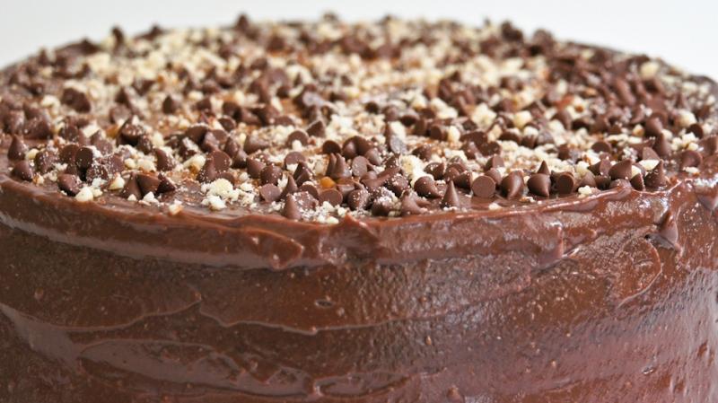 Pudín de chocolate cubierto de chocolate y arequipe, decorado con chispas de chocolate y almendra.